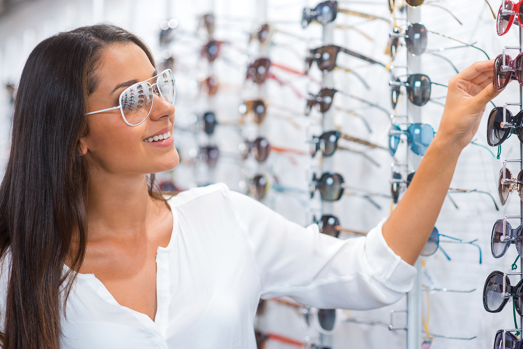 Woman choosing sunglasses. Beautiful young woman choosing sungla